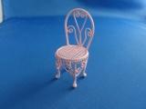 Roze metalen stoel voor het poppenkind